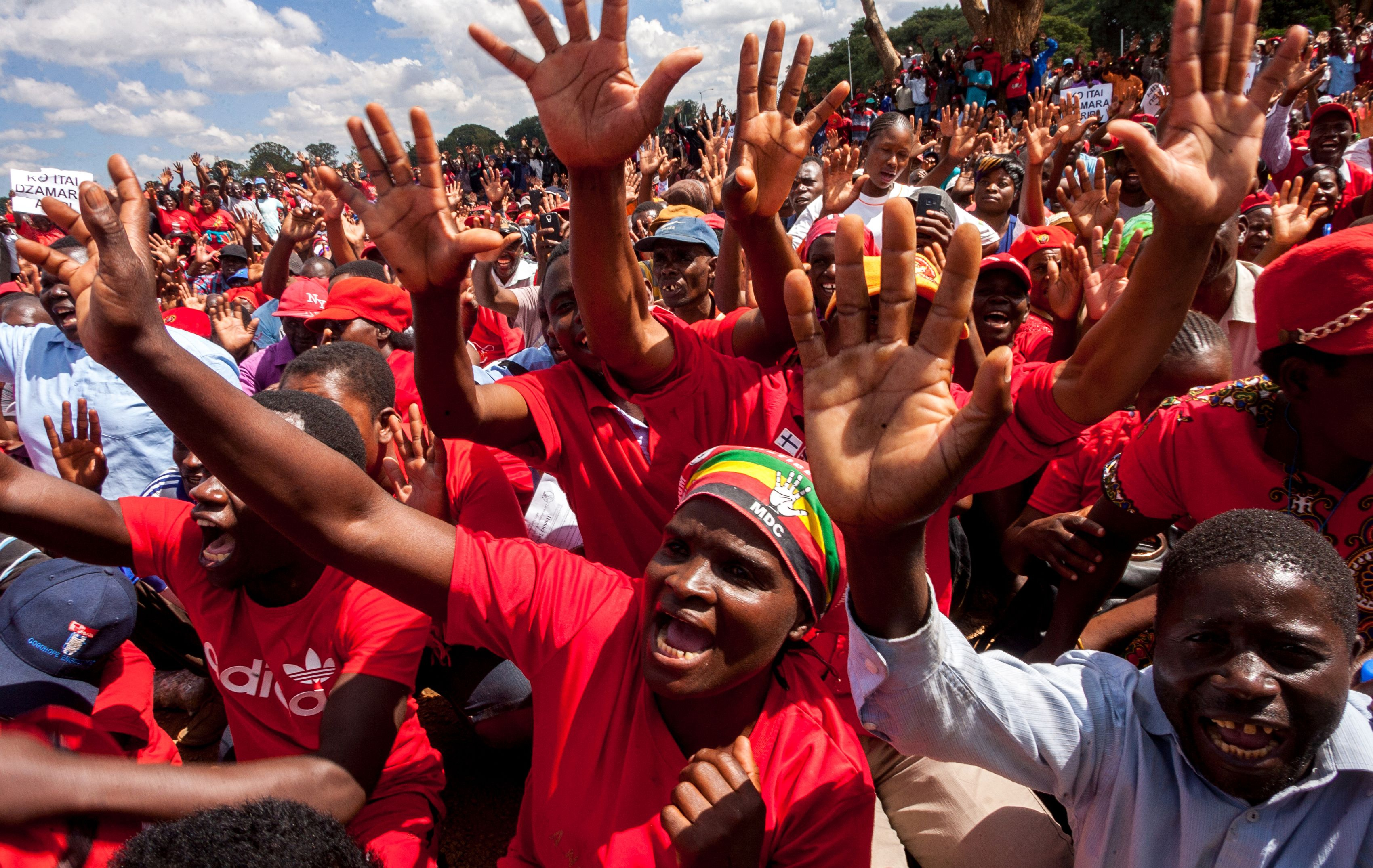 Movement for Democratic Change (MDC) supporters raise their hands in the party slogan during a demonstration by the opposition party in Harare on April 14, 2016. / AFP / JEKESAI NJIKIZANA        (Photo credit should read JEKESAI NJIKIZANA/AFP/Getty Images)